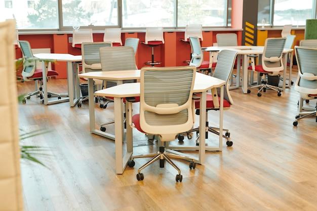 Интерьер современного большого открытого офиса со множеством стульев у столов и вдоль подоконников без рабочих или менеджеров.