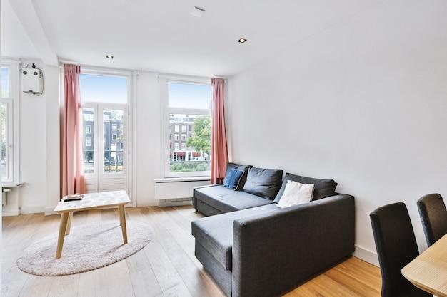 Интерьер современной гостиной с удобным диваном и деревянным столом в квартире