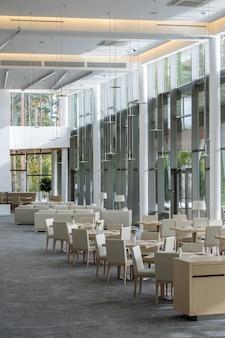 창문을 따라 서 있는 의자가 있는 테이블 그룹을 포함한 현대적인 대형 비즈니스 센터의 현대적인 레스토랑 내부