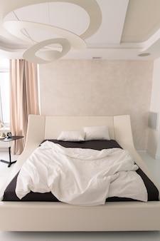 Интерьер уютной спальни с удобной двуспальной кроватью с геометрической люстрой наверху, будильником на столике и бежевой занавеской на окне