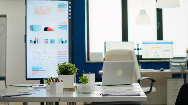 브레인스토밍을 위한 회의 테이블, 현대적이고 세련된 의자 및 데스크탑 모니터가 있는 아늑한 조명 회사 룸 내부는 직원들을 위해 모두 준비되어 있습니다. 창의적인 작업 공간의 빈 넓은 사무실.