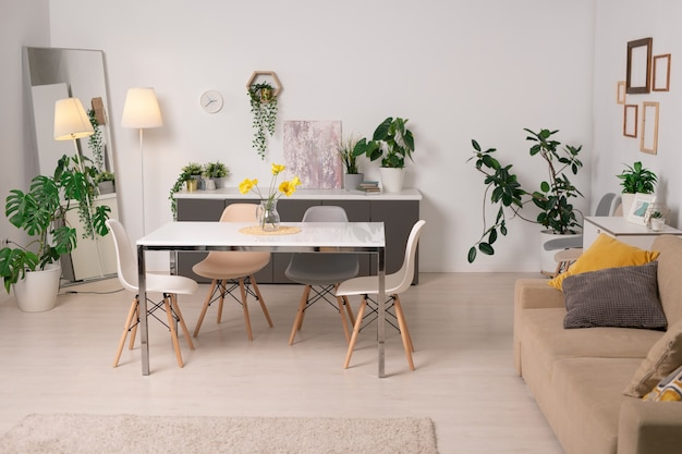 Интерьер уютной гостиной с обеденным столом, диваном, зелеными горшечными растениями и рамками на стенах