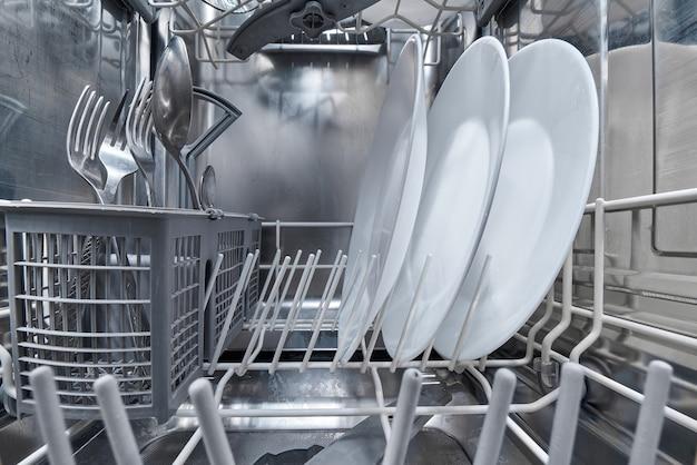 Интерьер посудомоечной машины с чистой посудой после мытья.
