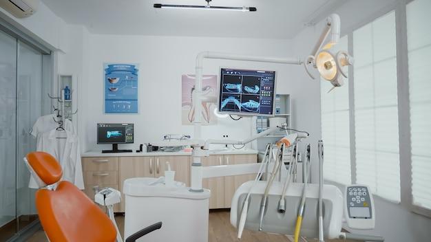 モニターにx線を備えた空の口腔病学歯科矯正医のオフィスルームの内部