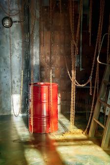 チェーンと赤い樽のある工場工業店の内部は窓からの日光に照らされています