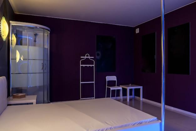 Интерьер гостиничного номера в резиденции обставлен современно, где мужчины нанимают проституток для мужских утех. эскорт, проституция, приватные танцы, концепция стриптиз-шоу. скопируйте космический фон
