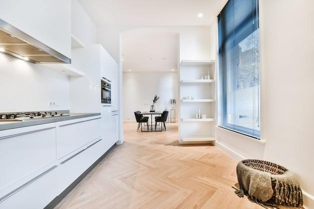 흰색 미니멀 한 캐비닛과 내장 된 가전 제품 및 테이블이있는 식당으로가는 통로가있는 집 부엌 방의 내부