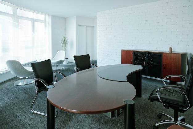 Интерьер большого современного зала заседаний со стульями вокруг дизайнерского стола, двумя белыми креслами рядом и деревянным шкафом вдоль кирпичной стены