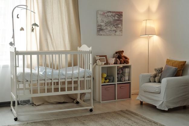ゆりかごと家具が付いている赤ん坊の大きい現代的な部屋の内部