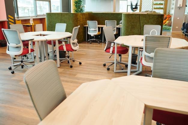 Интерьер большого открытого офиса с множеством стульев у различных столов напротив зоны отдыха с диваном и подушками, вокруг которой никого нет.