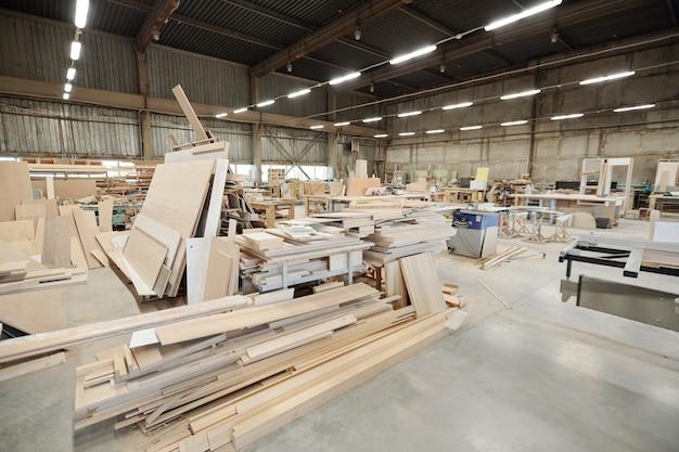 Интерьер большой мастерской современной мебельной фабрики с рабочими местами, состоящими из верстаков с рабочими принадлежностями