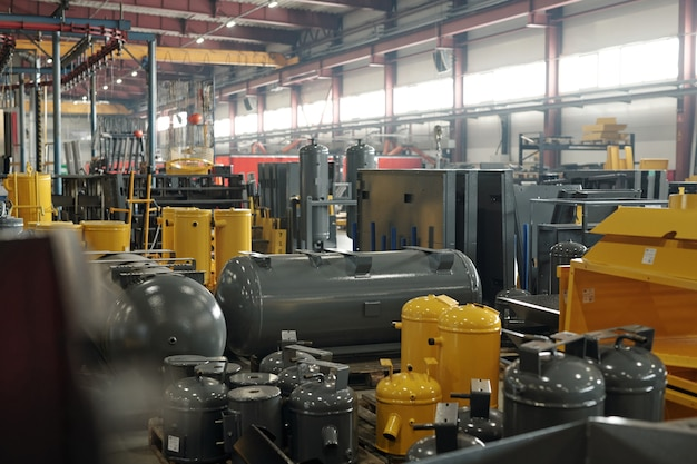 Интерьер большой мастерской или склада современного завода или промышленного предприятия с новым оборудованием серого и желтого цветов