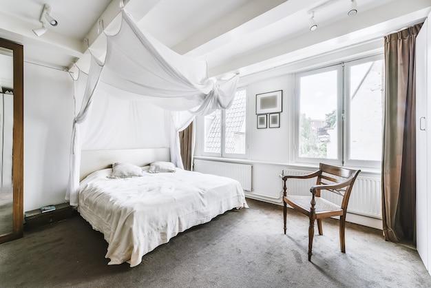 柔らかな日光の下で大きなベッドの上にカーペットの床と白い天蓋のある明るい寝室のインテリア