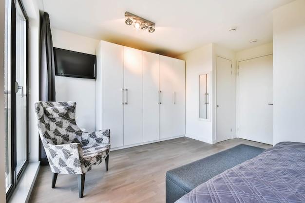퀸 사이즈 침대와 큰 창문에 대한 고전적인 안락 의자가있는 밝은 침실 인테리어