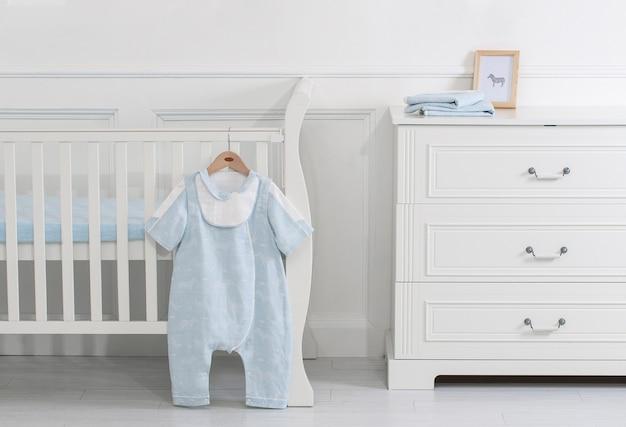 Интерьер светлой уютной детской комнаты с детской кроваткой и постельными принадлежностями