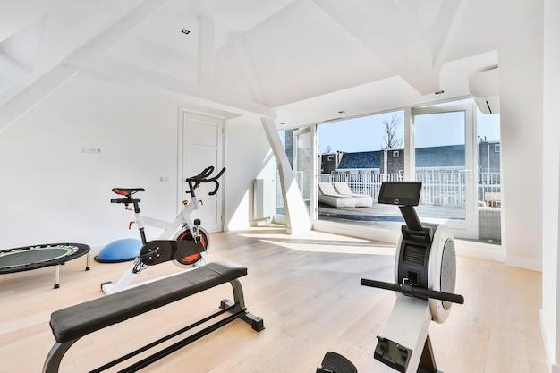 벤치 및 사이클링 머신의 체육관 장비가 비치 된 라이트 하우스 룸의 내부