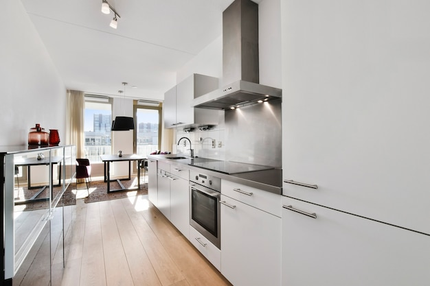 낮에는 현대적인 아파트의 식당 근처에 현대적인 찬장과 가전 제품을 갖춘 밝은 주방 인테리어