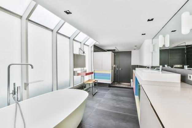 Интерьер светлого туалета с чистой ванной и красочными шкафами с раковинами в современной квартире