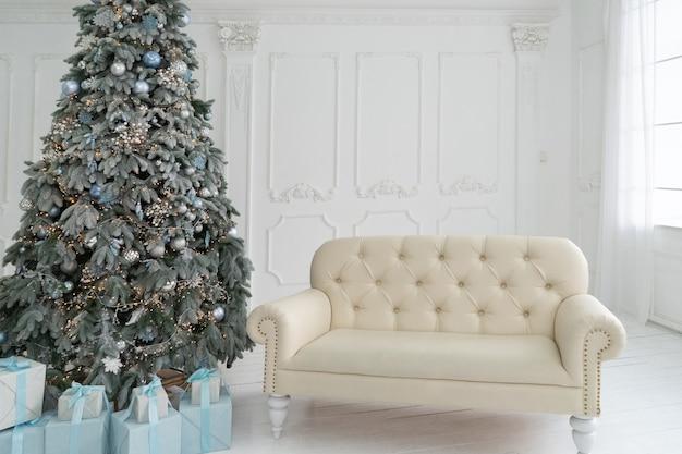 Интерьер гостиной с елкой и белым диваном на белой стене