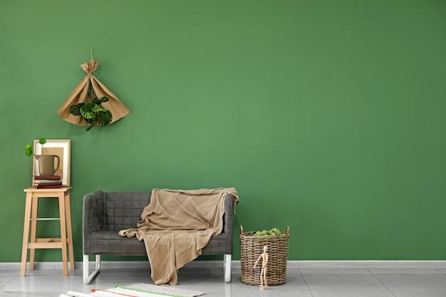 色の表面近くの快適なソファ付きのリビングルームのインテリア