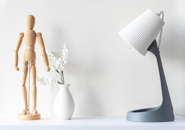 거실의 인테리어입니다. 나무 마네킹, 장식 식물이 있는 꽃병, 흰색 나무 책상 위의 램프, 모형, 최소 구성, 텍스트 공간
