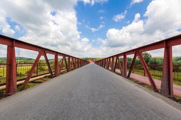 화창한 날에 다리의 금속 구조의 내부. 우크라이나의 다리에서 무한대에 대한 관점