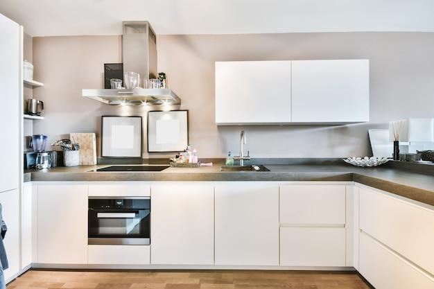 明るいアパートのシンプルな食器棚とモダンな電化製品を備えたミニマリストスタイルのキッチンのインテリア