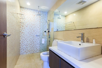 Interior of modern bathroom with shower, toilet and wash basin in beige natural