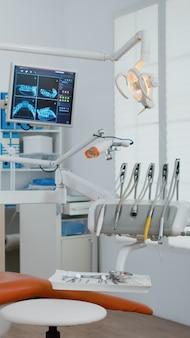 Интерьер современного оборудования устного кабинета с рентгеновским снимком зубов на мониторах
