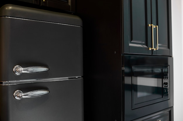 冷蔵庫付きのモダンなキッチンのインテリア。レトロな黒の冷蔵庫。