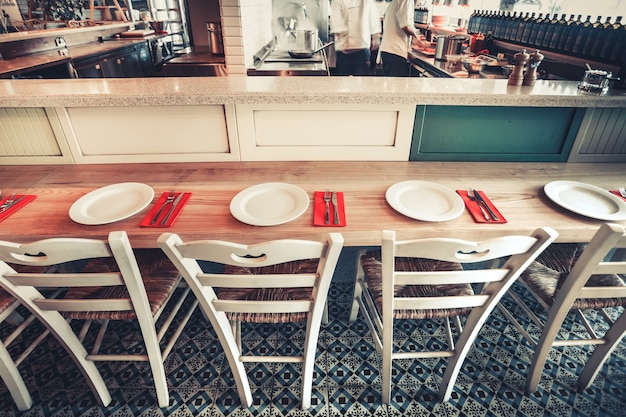 Интерьер современного ресторана со стульями и посудой