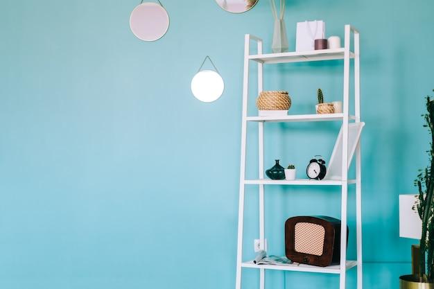 랙 선반과 파란색 벽이있는 흰색 현대적인 객실의 인테리어.