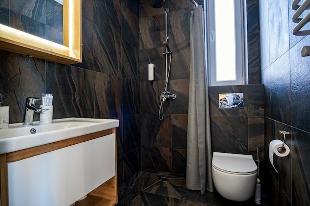 Интерьер современной стильной ванной комнаты с черными плиточными стенами, занавеской для душа и деревянной мебелью с умывальником и большим зеркалом с подсветкой.