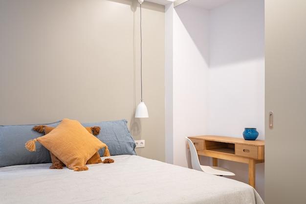 小さな作業台と窓のある新しい寝室のインテリア。心地よく落ち着いた色調の明るいお部屋