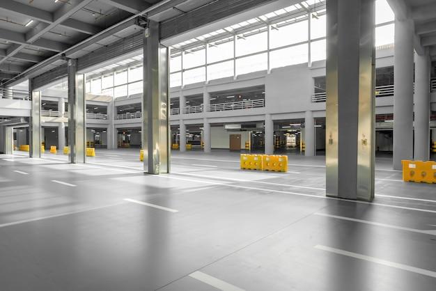 Интерьер гаража с автомобилем и свободная автостоянка в парковочном здании