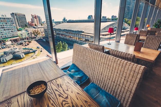 Интерьер ресторана с большими окнами и панорамным видом на центр киева, украина, европа