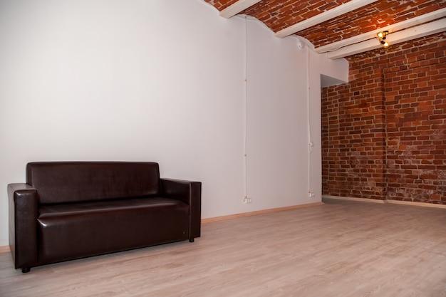 部屋のインテリアは、装飾的な赤レンガの壁と家具を備えたロフトスタイルでデザインされています。広いスペースと装飾的な要素を備えた工業デザインのグランジインテリア。テキストの著作権スペース