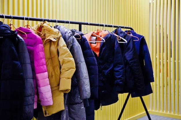 黄色の背景で、施設の訪問者のための屋外の衣類を保管する部屋のインテリア。ワードローブ、多くのハンガー服の施設、上着を残し、服を脱ぎながら部屋に入る。コピースペース