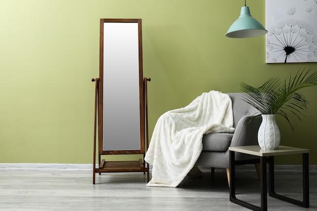 안락 의자, 테이블 및 거울이있는 방의 내부