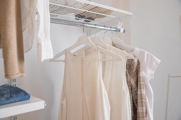 スタイリッシュな洋服とアクセサリーを備えたショールームのインテリアドレッシングルームのラックに掛かっている女性の洋服のコレクション