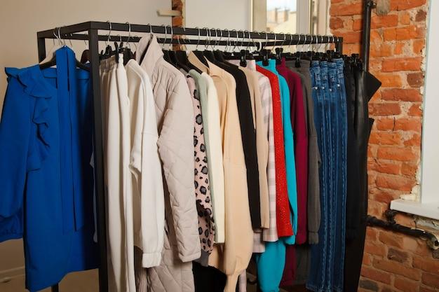 スタイリッシュな服を着たショールームのインテリア。屋内のレンガの壁と窓の近くにスタイリッシュな服を着たワードローブラック。ショールームの明るい美しさの色のドレスコレクションの詳細。テキスト用のスペースをコピーする