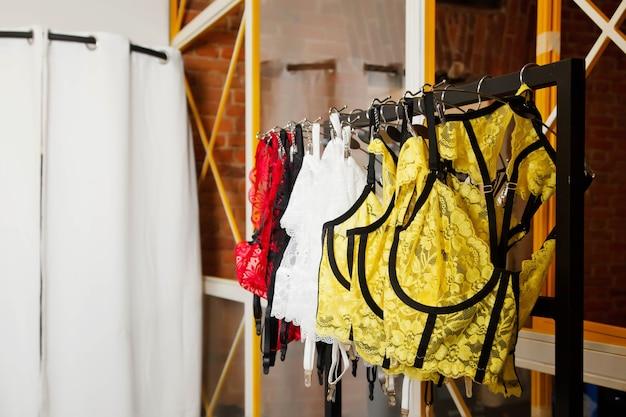 Интерьер выставочного зала с одеждой нижнего белья. гардеробная вешалка со стильным нижним бельем у кирпичной стены и кабинка для переодевания в помещении. детали коллекции яркой красоты цветной одежды в выставочном зале. копировать пространство