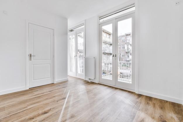 Интерьер просторной пустой комнаты с белыми стенами и закрытыми дверями в современной квартире