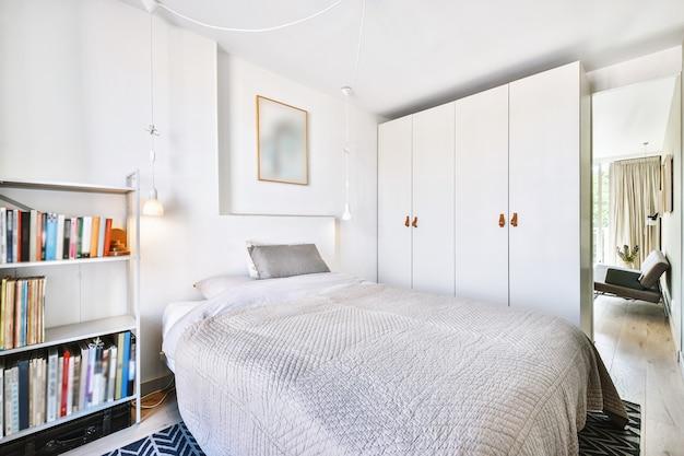 화창한 낮에 현대 아파트의 발코니가있는 넓은 조명 침실 인테리어