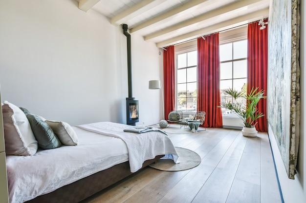 Интерьер просторной светлой гостиной с удобной кроватью и камином на фоне окон с красными шторами
