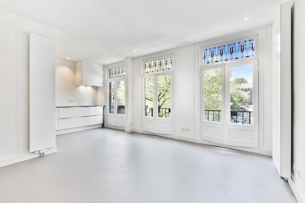 현대 아파트의 큰 장식용 창문과 카운터가있는 넓은 조명 공간의 내부