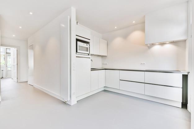 Интерьер просторной светлой комнаты с кухонной мебелью и пустой столовой в современной квартире