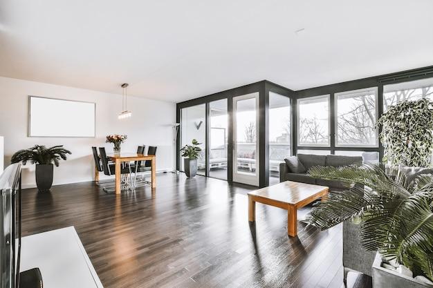Интерьер просторной комнаты со стильной мебелью против окон на балкон в современной квартире
