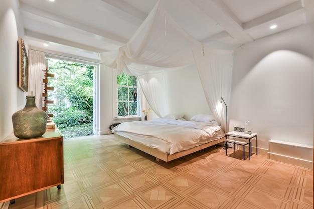 흰색 캐노피 아래에 퀸 사이즈 침대가있는 넓은 흰색 침실 내부와 녹색 정원으로 이어지는 열린 출입구