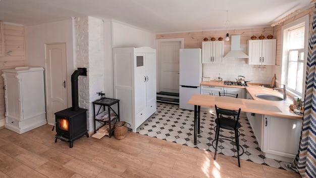 居心地の良い民家にあるスカンジナビアスタイルの暖炉のあるスタジオルームのインテリア。リビングルームとキッチンが一体となっています。